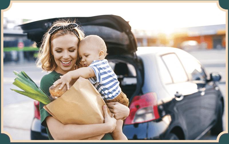 Familienmanagerin hat eine Einkaufstüte und ein Kind auf dem Arm.