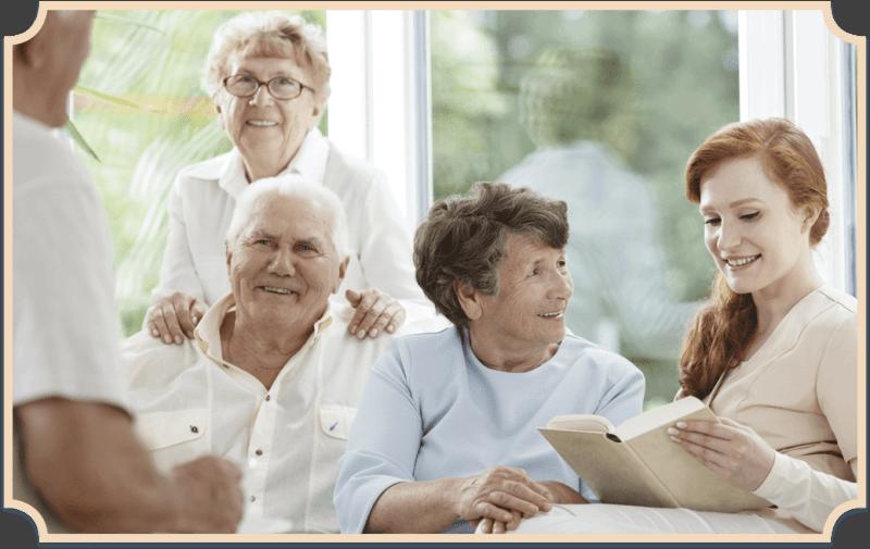 Seniorenunterstützung: Junge Frau liest Senioren vor.